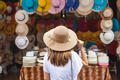 Young woman traveler looking for hat at the local market in Thailand - PhotoDune Item for Sale