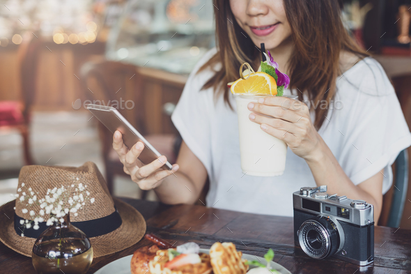 Young woman using smart phone and enjoy eating dessert in cafe on vacation - Stock Photo - Images