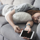 Young woman using smartphone at cozy home and sleeping on sofa in living room - PhotoDune Item for Sale