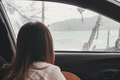 Sad young woman traveler inside the car in rainy day looking through the window at the beach - PhotoDune Item for Sale
