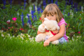 Adorable girl hugging her teddy bear in summer park - PhotoDune Item for Sale