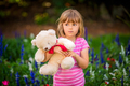 Adorable girl with a white teddy bear in a park - PhotoDune Item for Sale