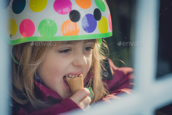 Girl with a helmet eating ice cream - Stock Photo - Images
