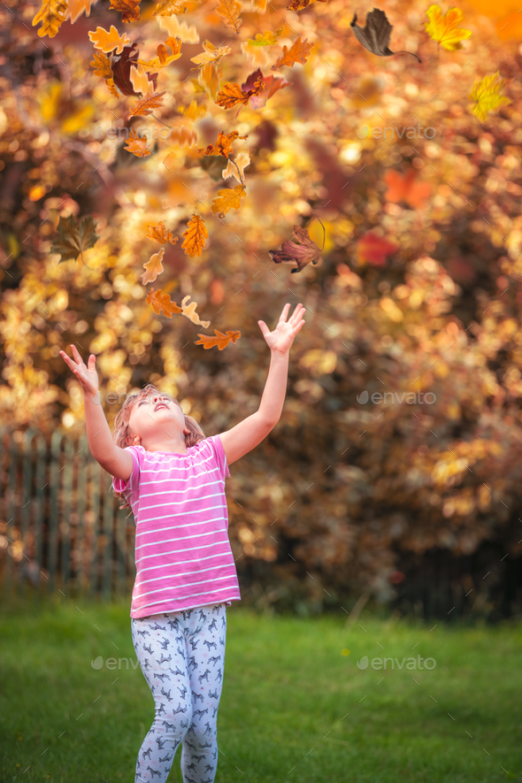 Girl catching leaves in autumn - Stock Photo - Images