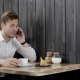 Young Man Id Talking on Smartphone. Casual Guy Is Using Cell Phone in a Cafe. Portrait of a Handsome - VideoHive Item for Sale