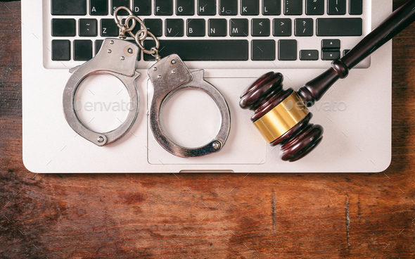 Handcuffs and a gavel on a computer on a wooden background, copy space. - Stock Photo - Images
