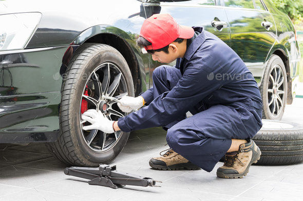 Mechanic replacing lug nuts changing tires on vehicle-3 - Stock Photo - Images