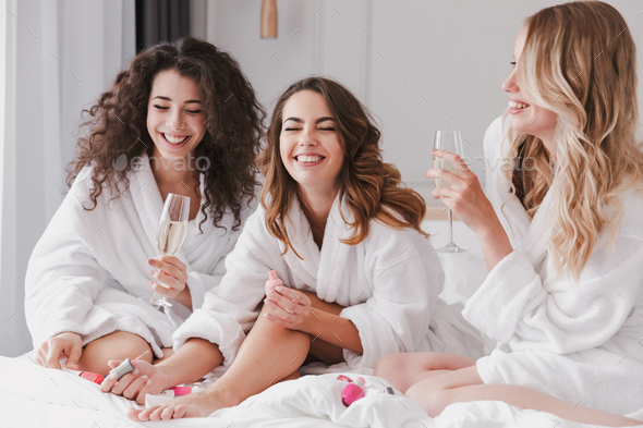 Image of cheerful three women 20s wearing housecoat sitting in l - Stock Photo - Images