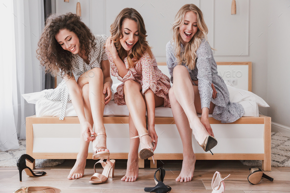 Picture of three gorgeous girls 20s wearing dresses trying on di - Stock Photo - Images