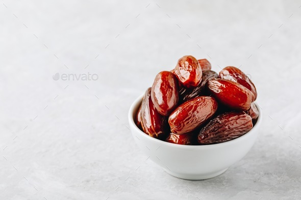 Dried dates in white bowl on grey background - Stock Photo - Images
