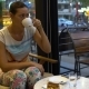 A Woman Sits at a Coffee Shop at a Table and Drinks Coffee - VideoHive Item for Sale