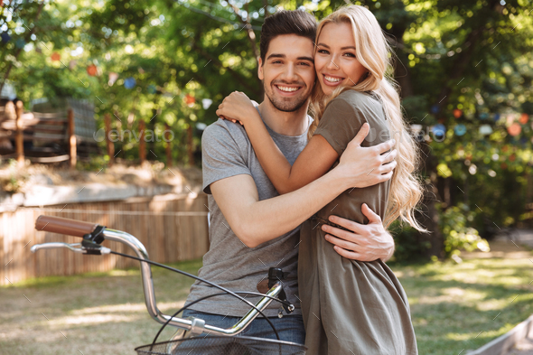 Smiling lovely young couple posing together with bicycle - Stock Photo - Images