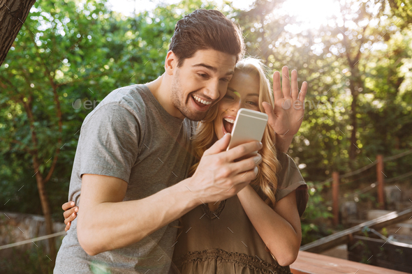 Picture of Smiling lovely couple posing together and making selfie - Stock Photo - Images
