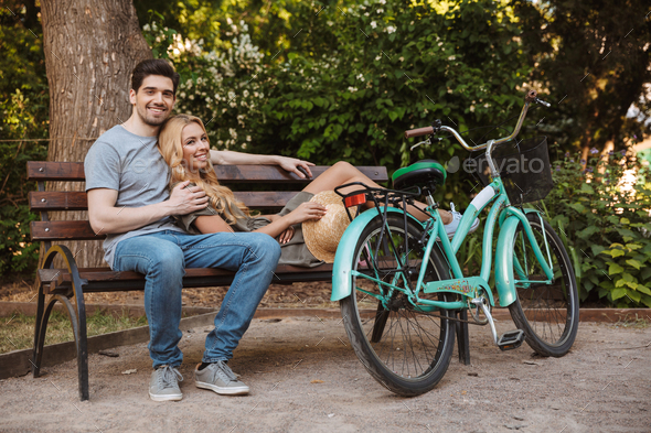 Pleased lovely young couple relaxing together on bench with bicycle - Stock Photo - Images