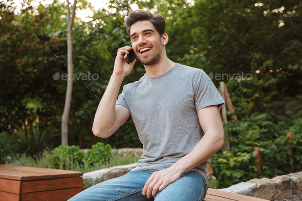 Picture of Happy man in casual clothes talking by phone - Stock Photo - Images