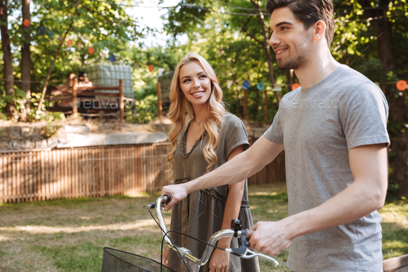 Side view of Happy young couple walks together with bicycle - Stock Photo - Images