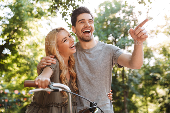 Cheerful lovely young couple posing together with bicycle - Stock Photo - Images