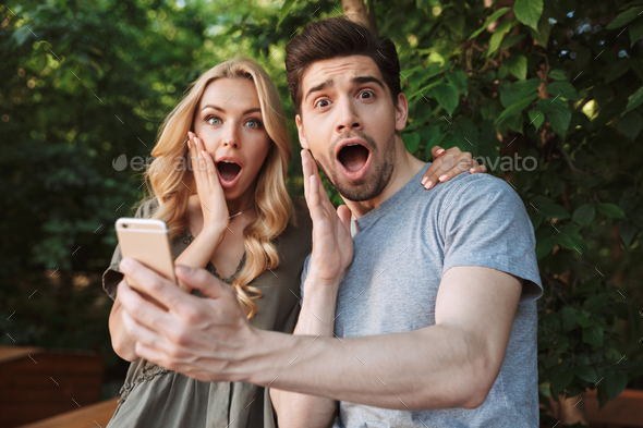 Surprised young couple taking a selfie together - Stock Photo - Images