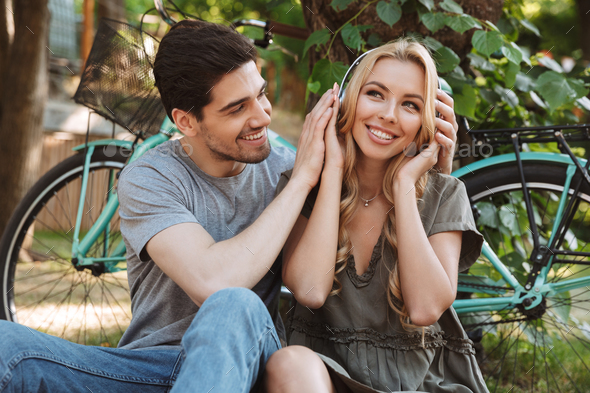 Picture of Happy young couple sitting together and listening music - Stock Photo - Images
