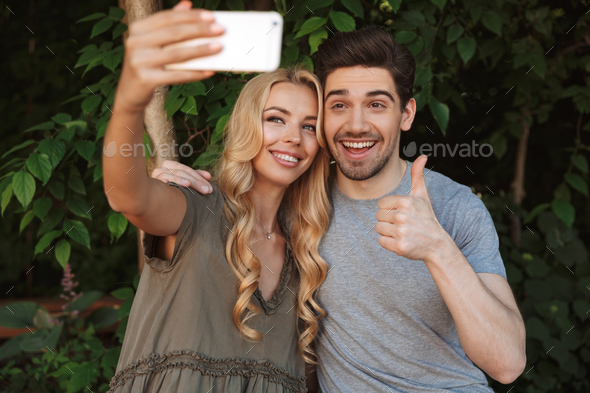 Cheerful young couple taking a selfie together - Stock Photo - Images