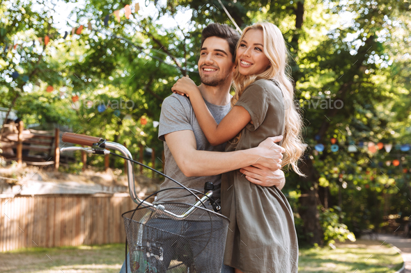 Joyful lovely young couple posing together with bicycle - Stock Photo - Images