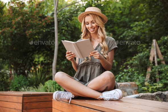 Smiling blonde woman in straw hat reading book - Stock Photo - Images