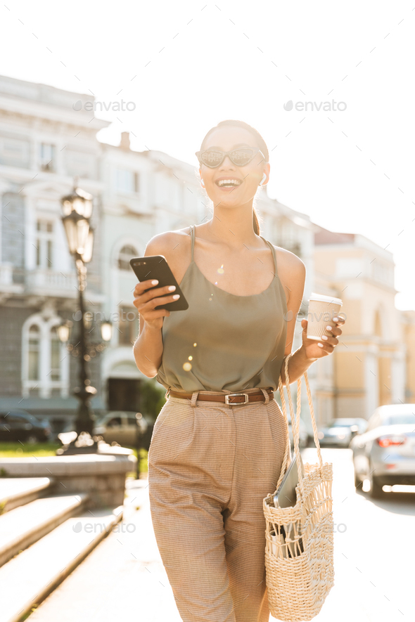 Portrait of smiling brunette woman wearing casual summer outfit, - Stock Photo - Images
