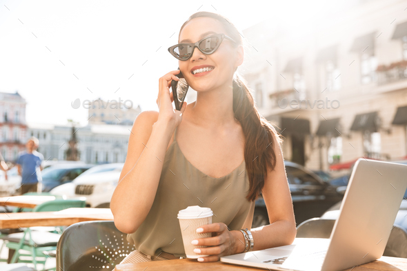 Photo of caucasian businesswoman wearing black sunglasses and dr - Stock Photo - Images