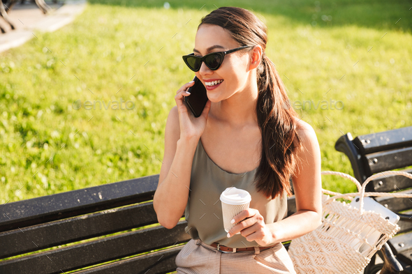 Photo of smiling brunette woman wearing casual summer outfit and - Stock Photo - Images