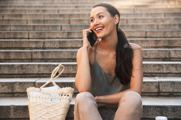 Pretty happy asian woman sitting on steps - Stock Photo - Images