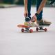 Skateboarder tying shoelace on skateboard - PhotoDune Item for Sale