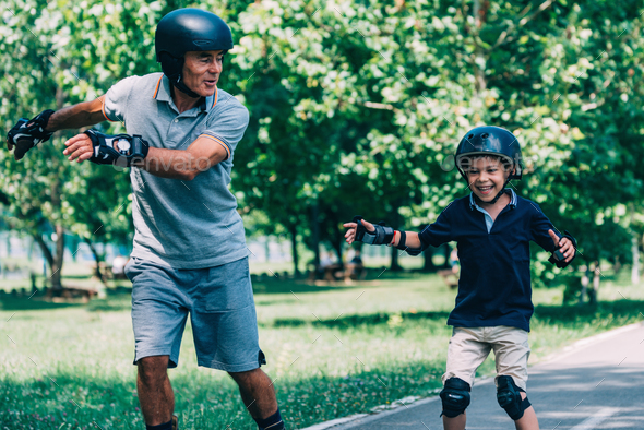 Roller skating race, grandfather and grandson having fun - Stock Photo - Images