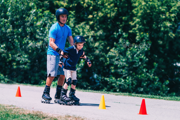 Senior man, teacher of roller skating with little boy - Stock Photo - Images