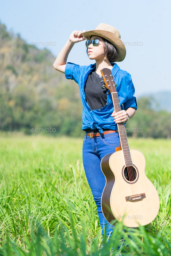 Woman stand carry her guitar in grass field_ - Stock Photo - Images