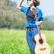 Woman stand carry her guitar in grass field_ - PhotoDune Item for Sale