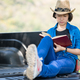 Woman wear hat and reading the book on pickup truck-3 - PhotoDune Item for Sale