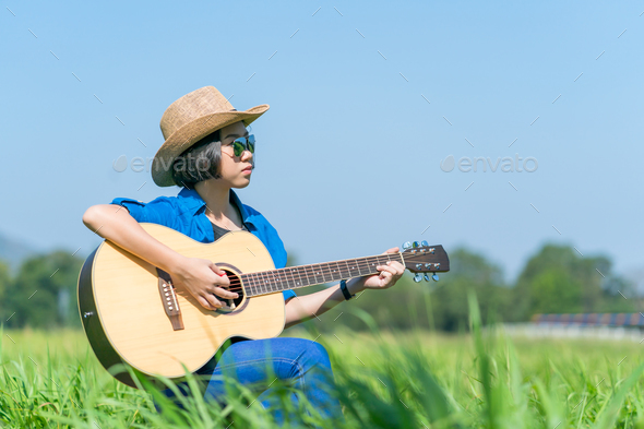 Women playing guitar in grass field_-8 - Stock Photo - Images