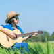 Women playing guitar in grass field_-8 - PhotoDune Item for Sale