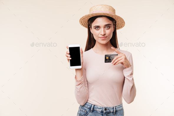 Amazing young pretty woman showing display of mobile phone holding credit card. - Stock Photo - Images