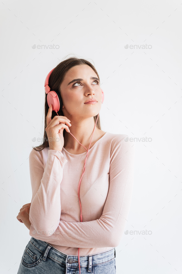 Portrait of a pretty young brunette girl listening to music - Stock Photo - Images