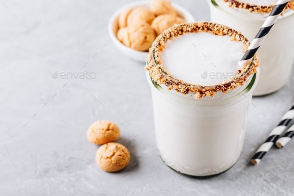 Vanilla milkshake with crispy cookies in glass mason jar on gray background - Stock Photo - Images