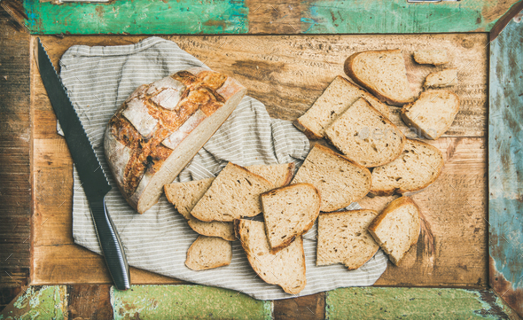 Flat-lay of sourdough wheat bread cut in slices in tray - Stock Photo - Images