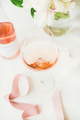 Rose wine in glass and bottle, pink ribbon, peony flowers
