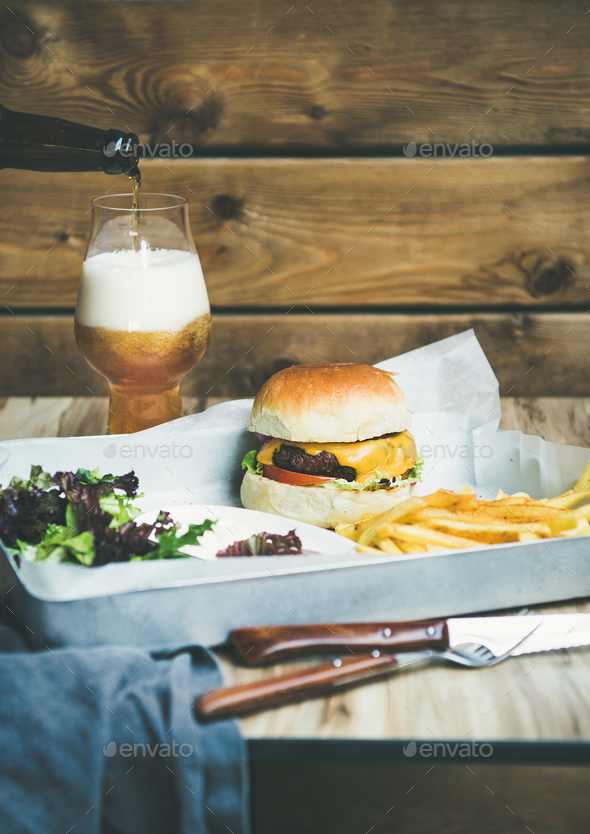 Beef burger, french fries, salad and glass of beer - Stock Photo - Images