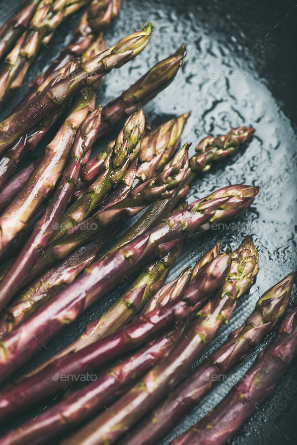 Fresh raw uncooked purple asparagus over dark background - Stock Photo - Images