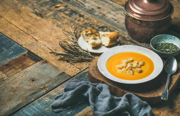 Warming pumpkin cream soup with croutons and seeds, wooden background - Stock Photo - Images