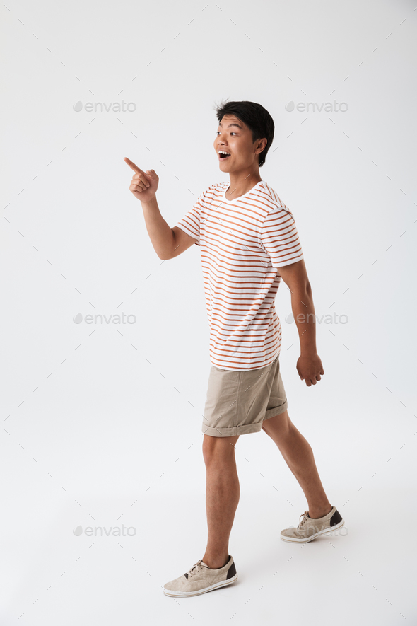 Full length portrait of a cheerful young asian man - Stock Photo - Images