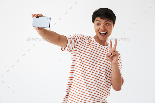 Portrait of a cheerful asian man showing peace gesture - Stock Photo - Images