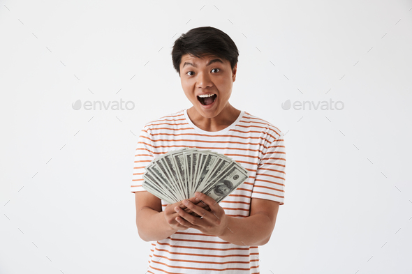Portrait of a happy asian man holding money banknotes - Stock Photo - Images