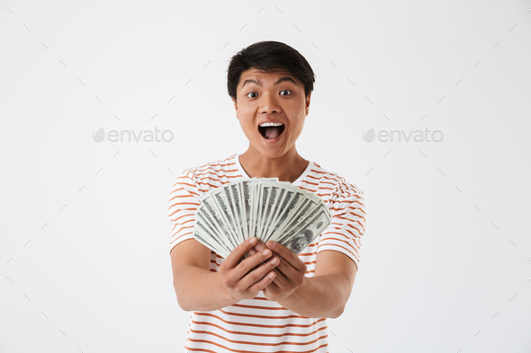 Portrait of a happy young asian man holding money banknotes - Stock Photo - Images